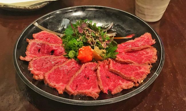 Tataki de boeuf Wagyu sur assiette noire