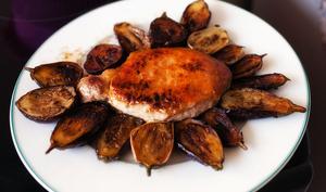 Côte de porc sur assiette entourée de petites aubergines