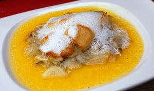 Saint-jacques au fenouil et écume de coco sur assiette blanche
