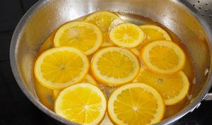 Tranches d'orange en train de confire dans le sirop